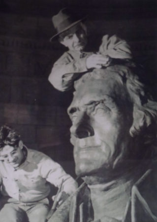 Attilio Contini and his son James apply a bronze patina to the plaster cast of the Thomas Jefferson in the memorial in Washington, D.C. Due to the war demand for rare metals, a plaster copy of the statue was installed by Attilio for the dedication of the memorial in 1943. The plaster remained in place until Attilio removed it in 1947 and it was replaced by the bronze statue seen today.